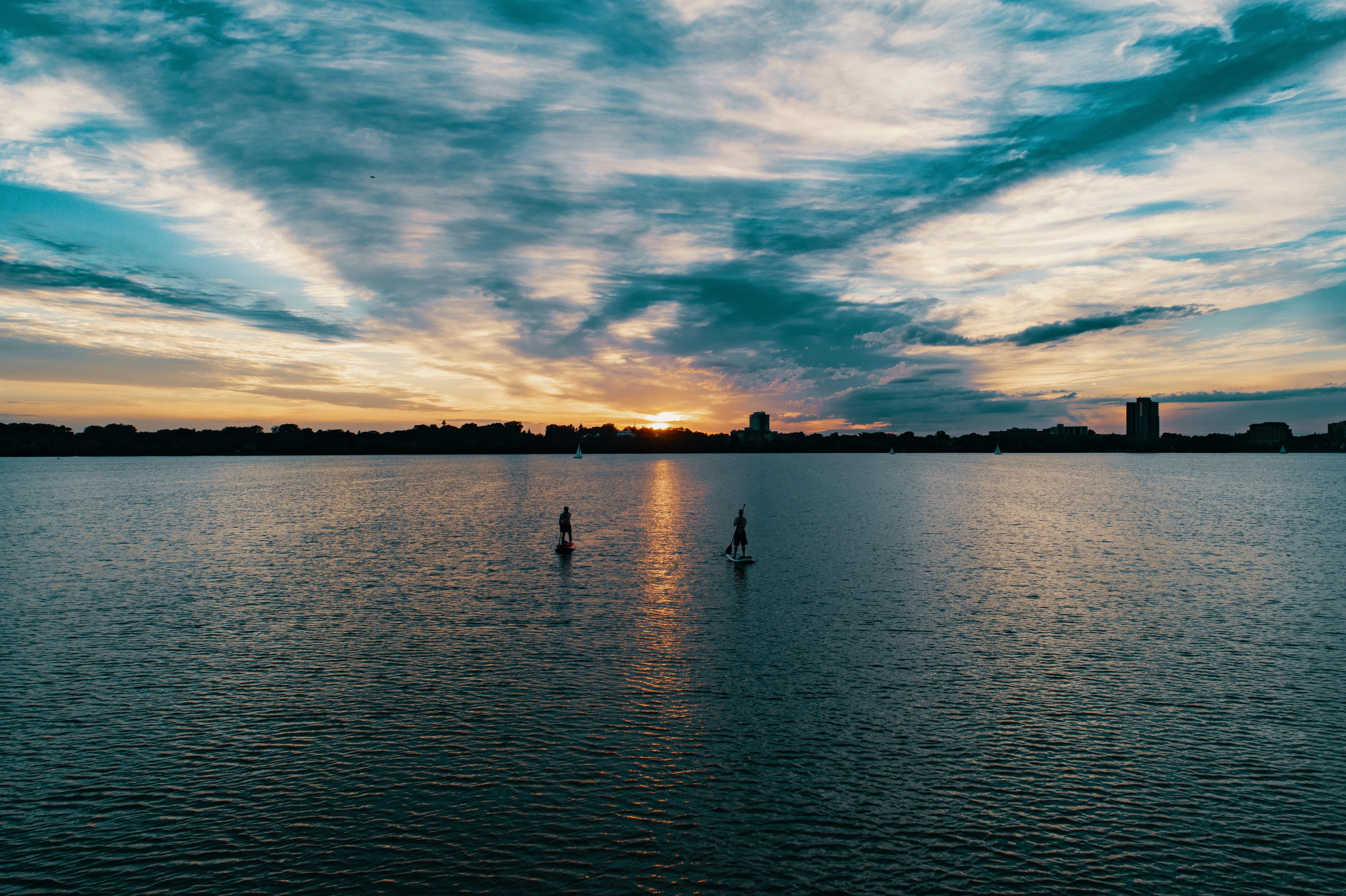 Moře během západu slunce s dvěma osobami na paddleboardech.