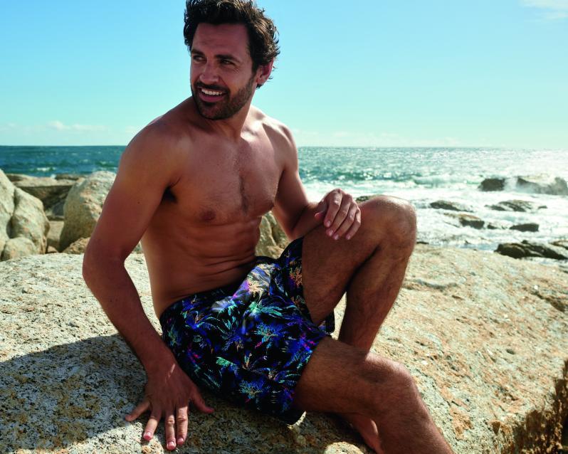 40 letý muž na pláži sedící na kameni v ekologických plavkách.