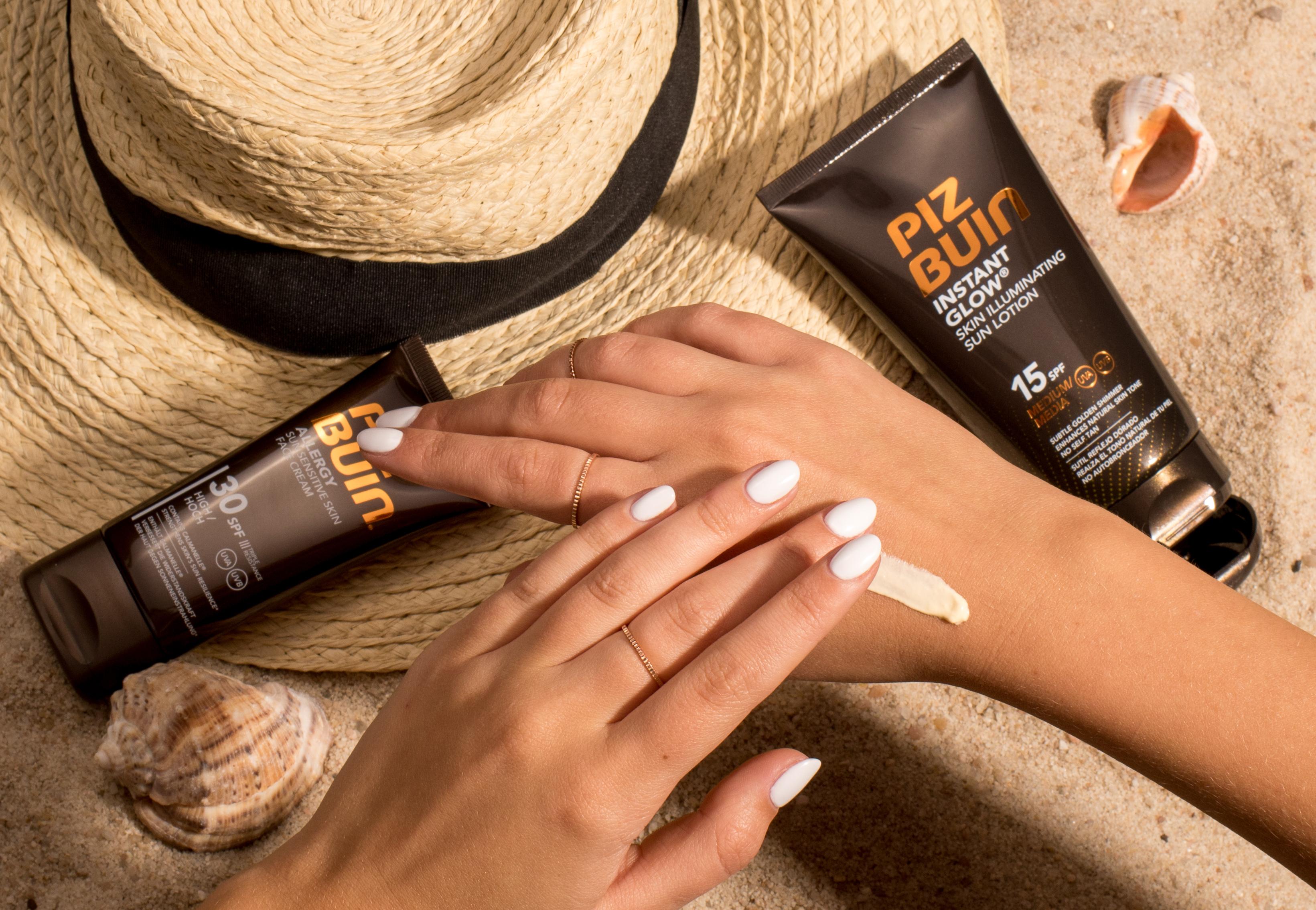 Ženské ruce na pláži, které rozmazávají opalovací krém. Slaměný klobouk na pláži a dva krémy na opalování Piz Buin.