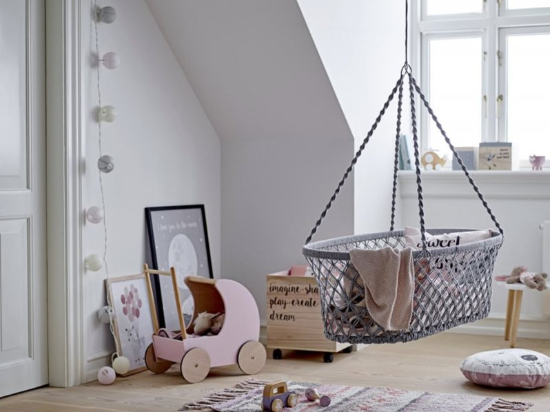 Skandinávský severský styl v dětském pokoji. Proutěný houpací koš postýlka pro miminko. Dřevěný kočárek, světlý dětský pokoj.