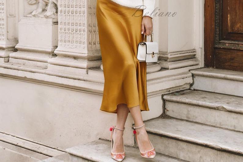 Žena v hořčicově žluté saténové slip sukni s bílou malou kabelkou a v lodičkách.