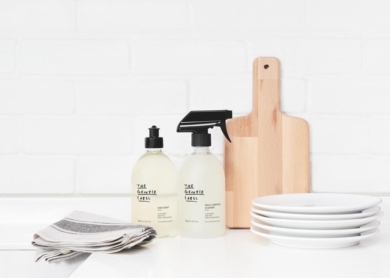 Lahvičky na kuchyňské lince vedle bílých talířů, dřevěného prkénka a utěrky
